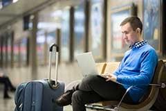 Business-traveler-waiting-on-laptop